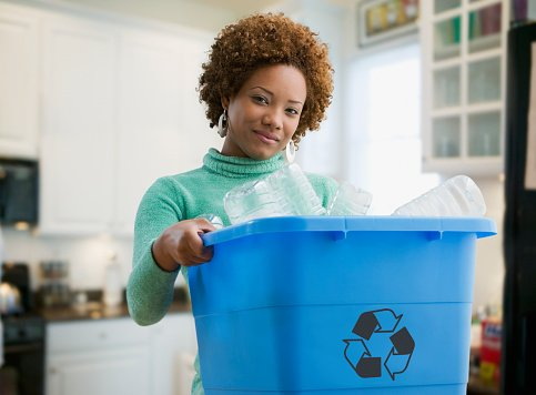 Photo of a beautiful woman carrying a recycling bin | Photo: Getty Images