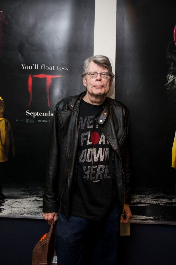 """Stephen King devant une affiche du film """"Ça"""". l Source : Getty Images"""