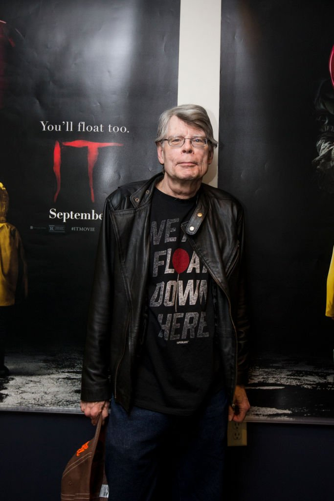 "Stephen King devant une affiche du film ""Ça"". l Source : Getty Images"