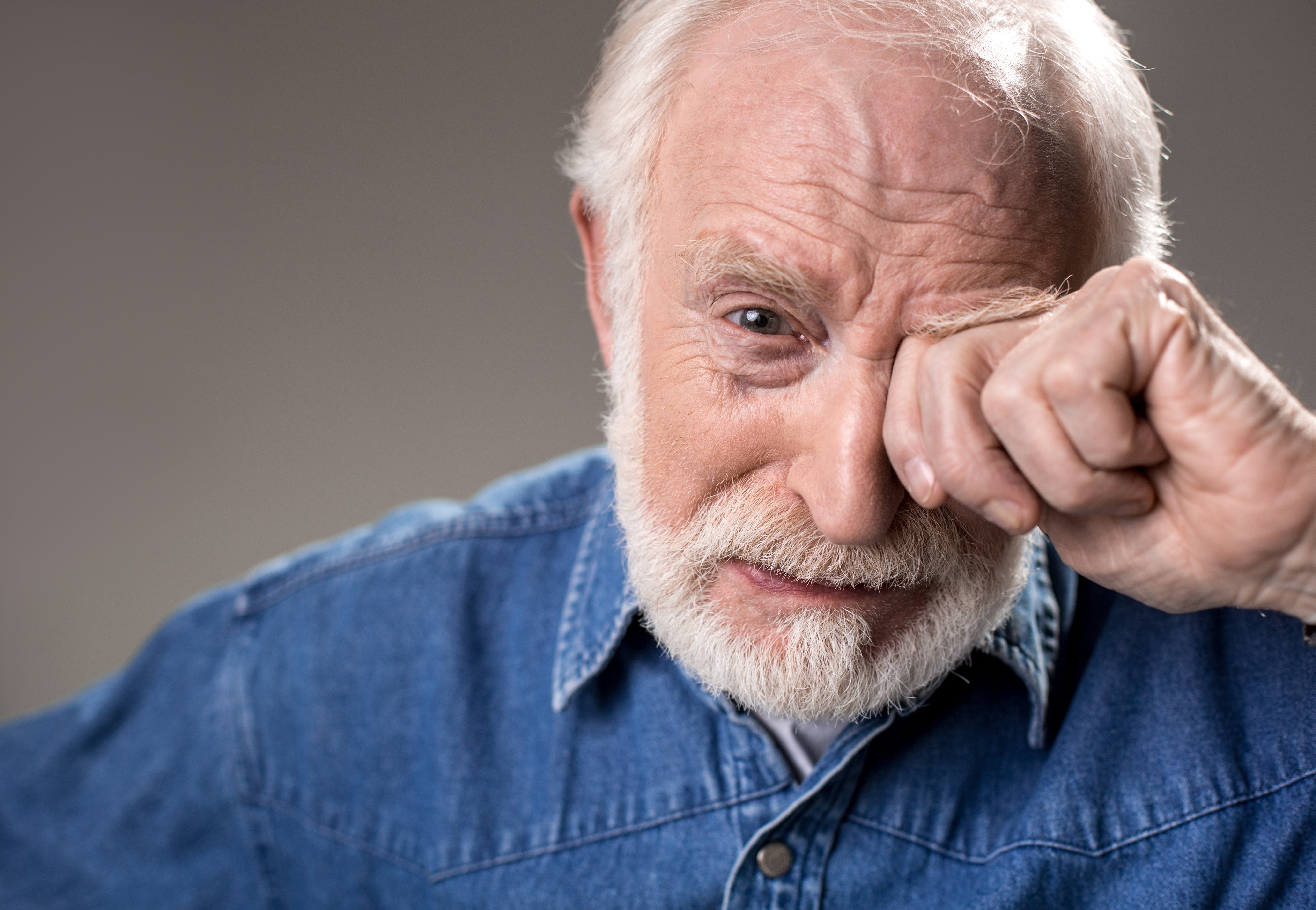 Older man in blue shirt covering one eye as he cries.|Source: Shutterstock