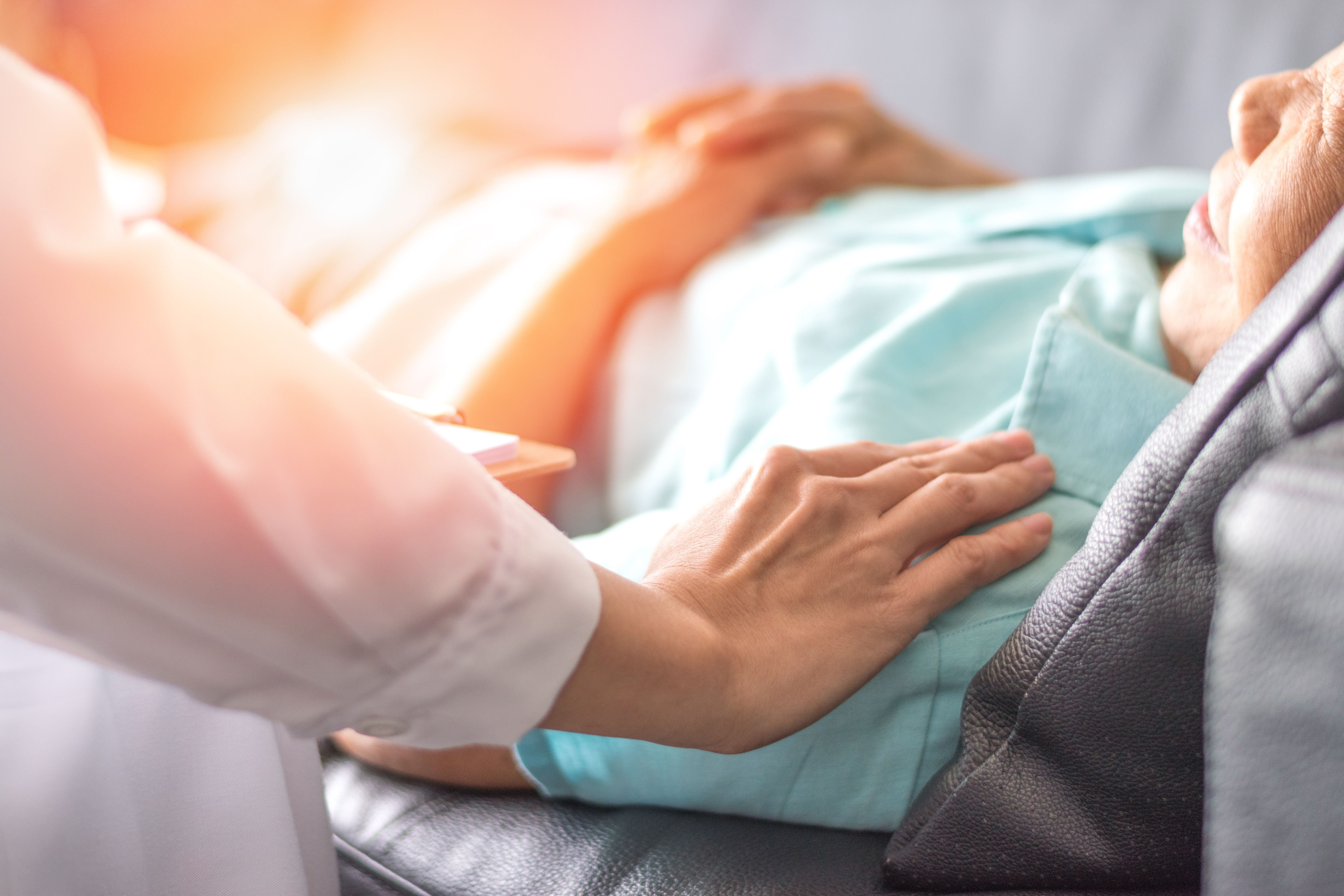 A doctor holding a patient in bed.  Source: Shutterstock
