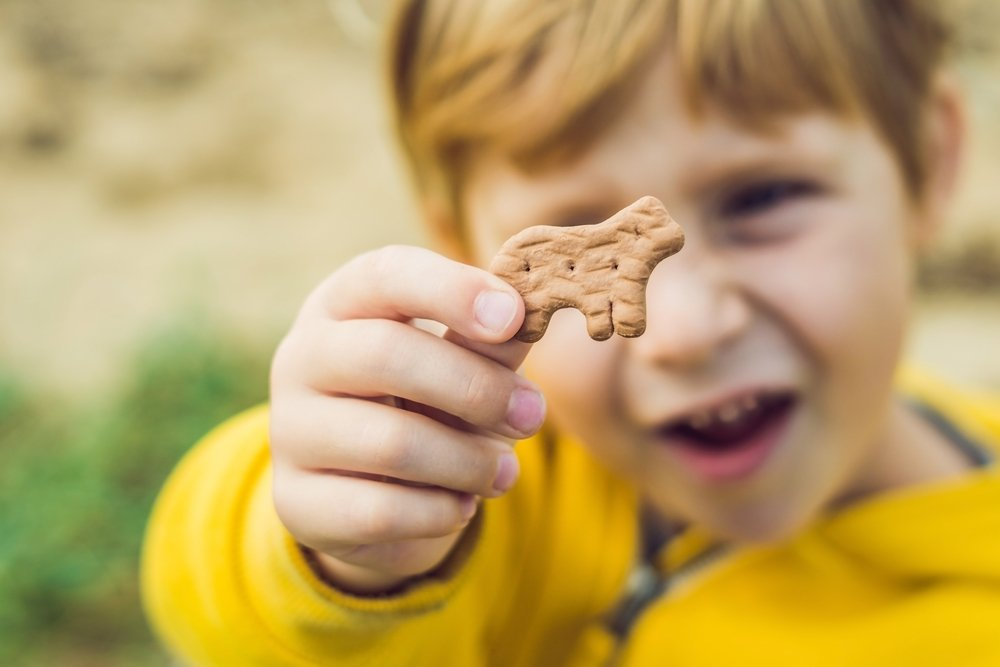 A child holding animal-shaped biscuit. | Source: Shutterstock.com