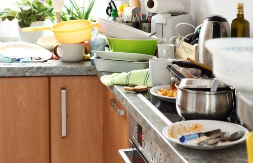 Kitchen counter piled with dirty dishes. | Source: Shutterstock.