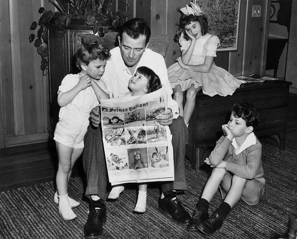 John Wayne reading a Prince Valiant comic with his four children, in Hollywood, California   Photo: Getty Images