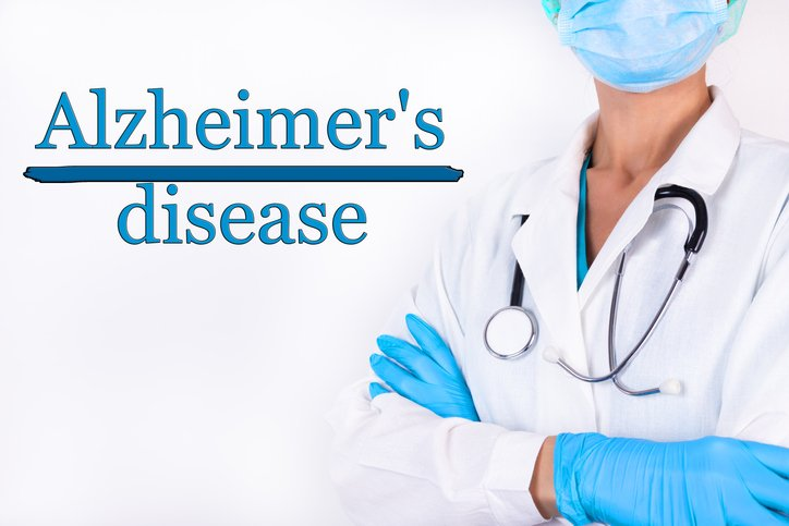 The inscription Alzheimers disease on a white background and a doctor with a stethoscope | Photo: Getty Images