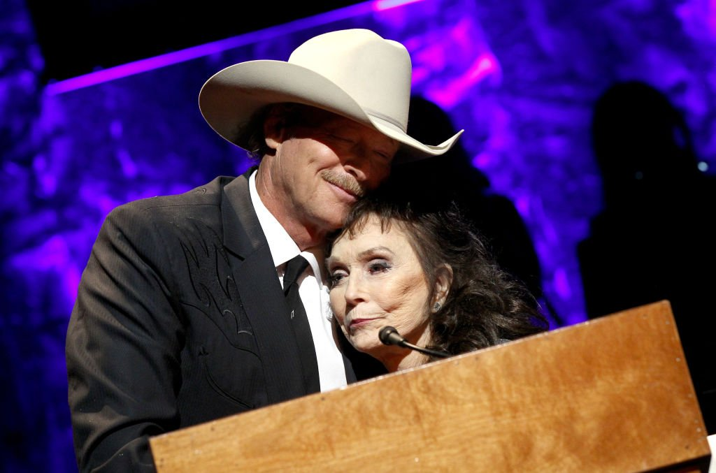Alan Jackson (L) is presented with a medallion by Loretta Lynn (R) onstage at the Country Music Hall of Fame and Museum Medallion Ceremony | Getty Images