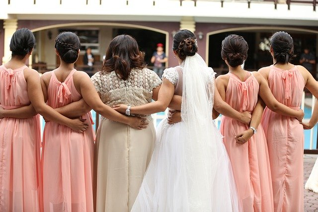Bride with bridesmaids in pink at a wedding | Photo: Pixabay