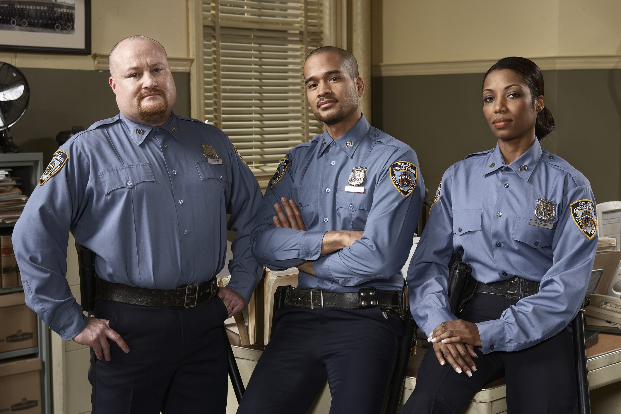 A potrait picture of three police officers at a police station. | Photo: Getty Images