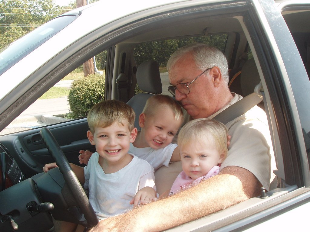 A grandfather in a car with his three grandchildren