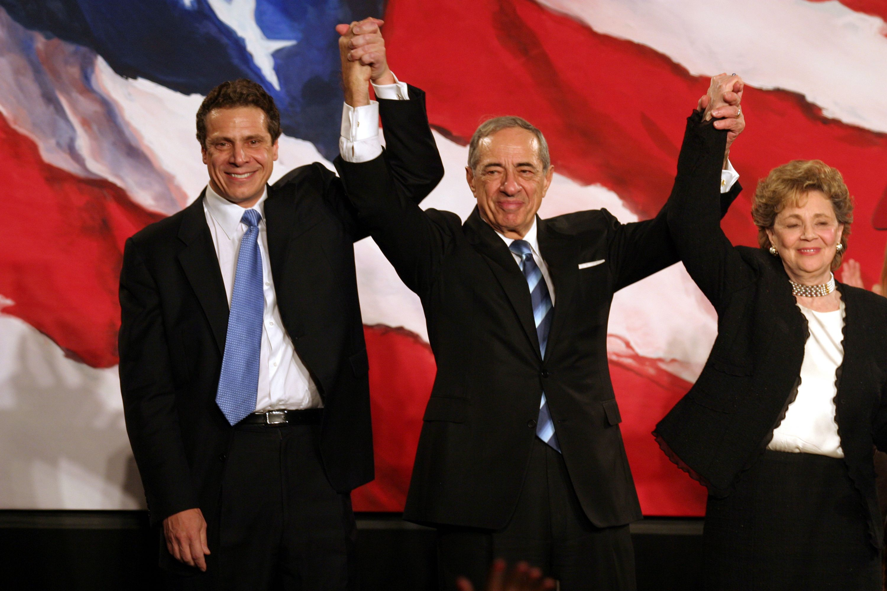 Andrew Cuomo, Mario Cuomo and Matilda Cuomo raise their hands in celebration during the Democratic Victory Celebration 2006| Photo: Getty Images