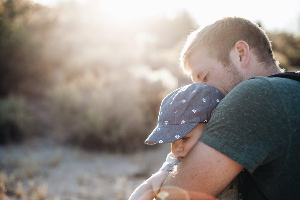 Un père tenant son fils dans ses bras. l Source: Pexels