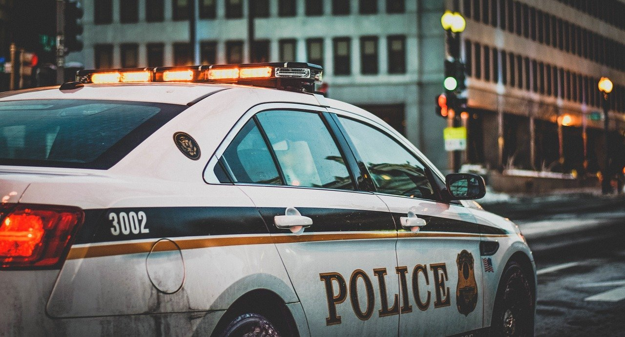 A police squad car with its lights on in an urban area.   Photo: Pixabay