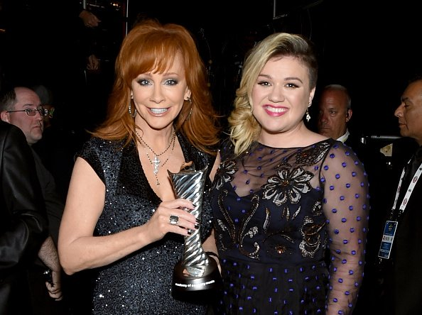 Reba McEntire and Kelly Clarkson posing backstage at the 50th Academy of Country Music Awards in Arlington, Texas.| Photo: Getty Images.