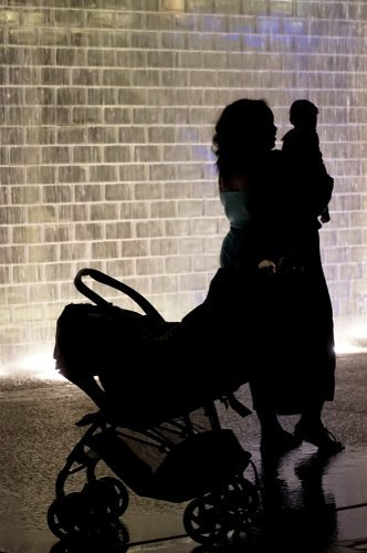 A mother and her baby standing next to a baby stroller at night. | Source: Shutterstock