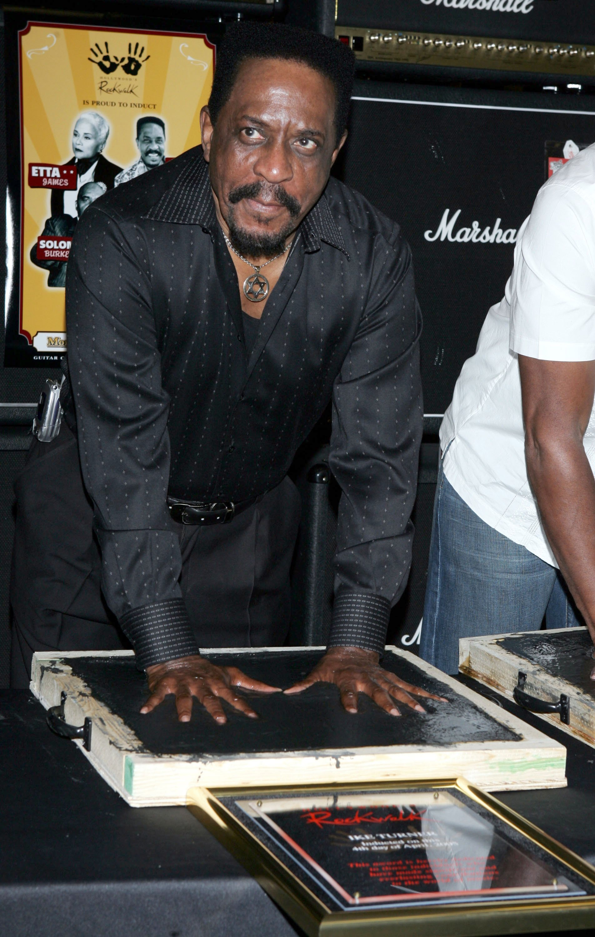 Ike Turner presses his hands into cement as he is inducted into the Hollywood Rockwalk on April 4, 2005. | Photo: GettyImages