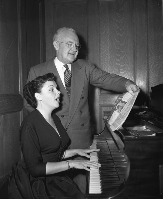Judy Garland at the piano with Los Angeles Mayor Fletcher Bowron advertising the Music Week | Source: Wikimedia Commons