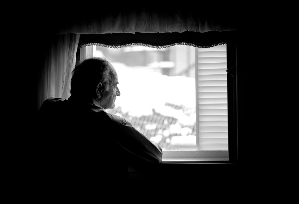 Lonely senior man looking at the window. | Photo: Shutterstock