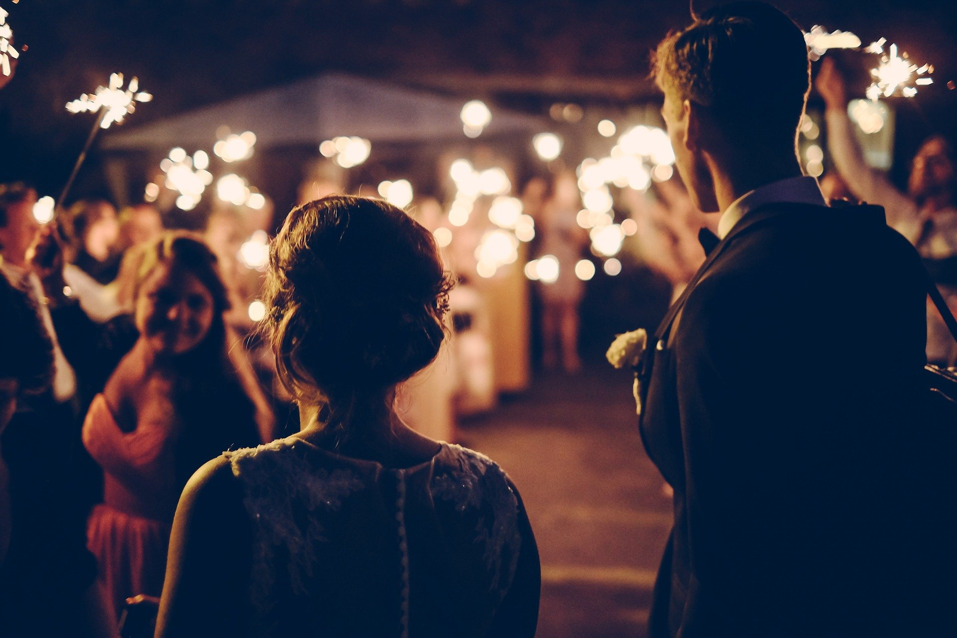 Man and woman looking on at wedding celebration. | Source: Pixabay
