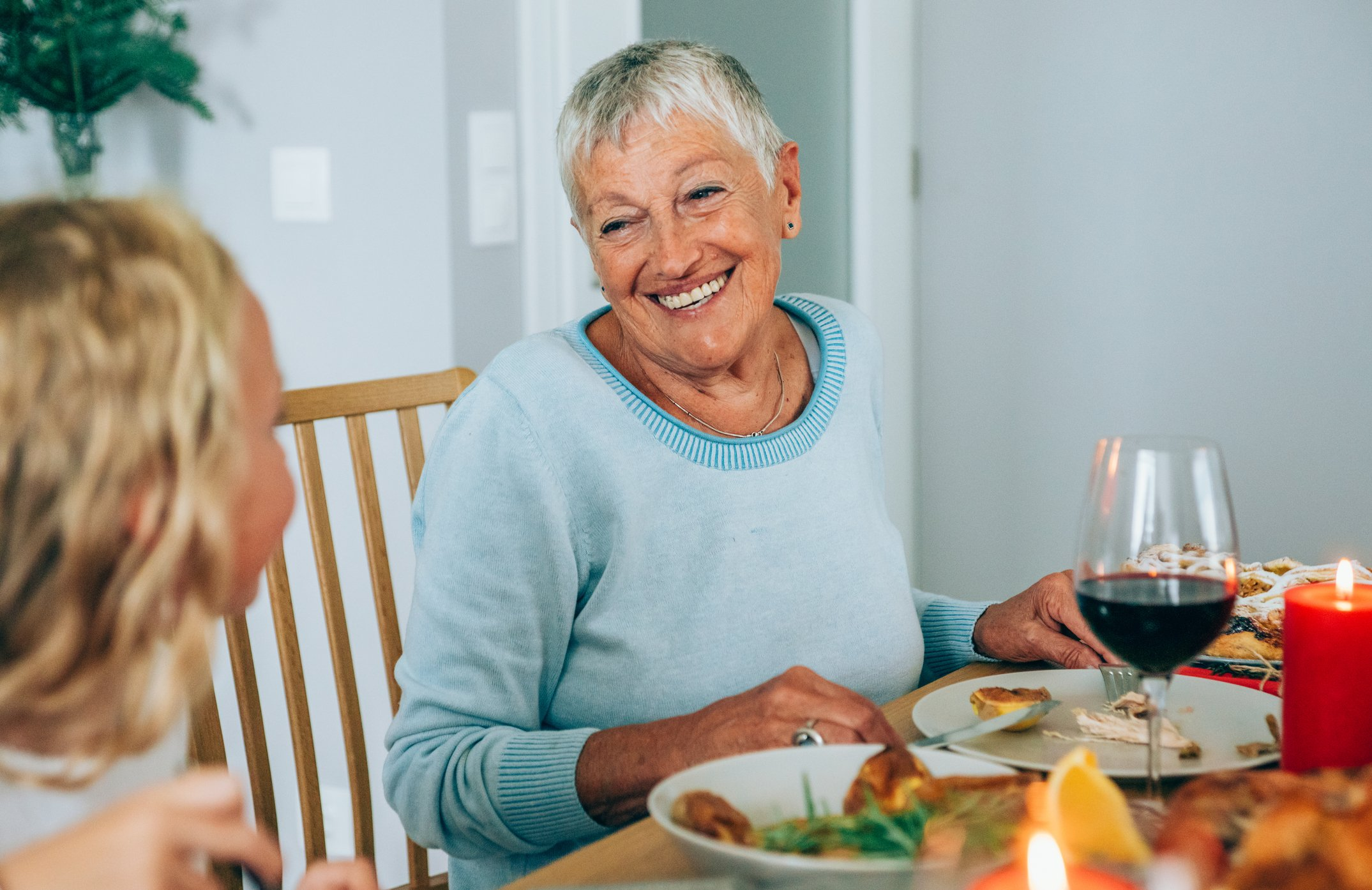 Photo of smiling senior woman during holiday dinner | Photo: Getty Images