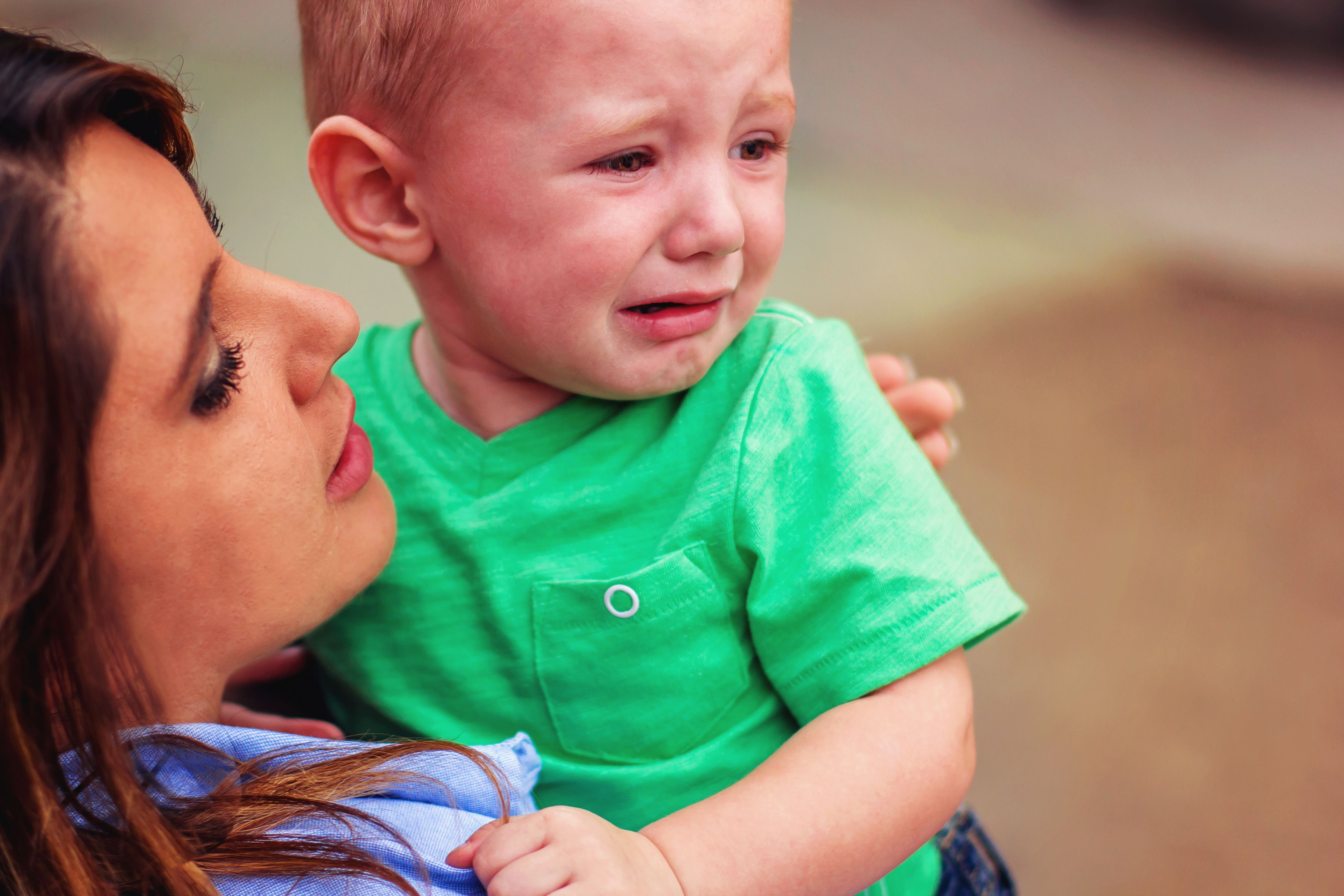 A woman holding a crying baby. │ Source: Shutterstock