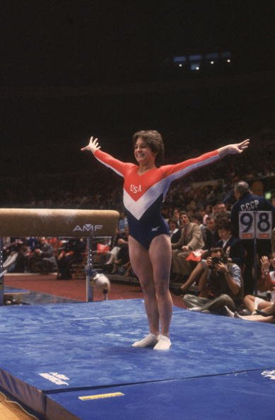 Full-length image of American gymnast Mary Lou Retton smiling while posing on the mat after her dismount from the balance beam at the Summer Olympic Games | Source: Getty Images