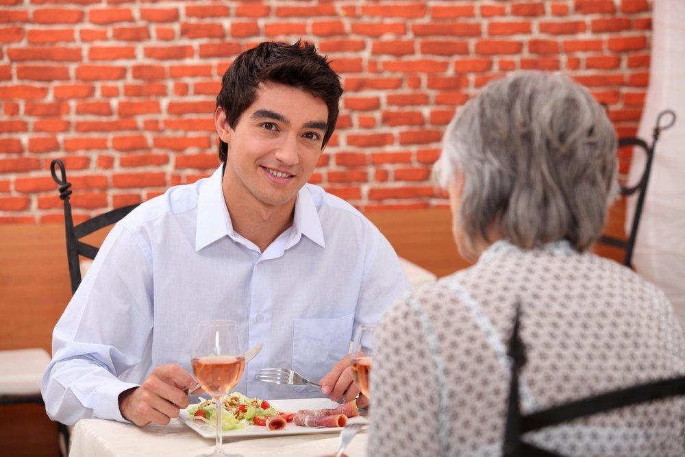 Une jeune homme déjeunant avec sa mère. | Shutterstock