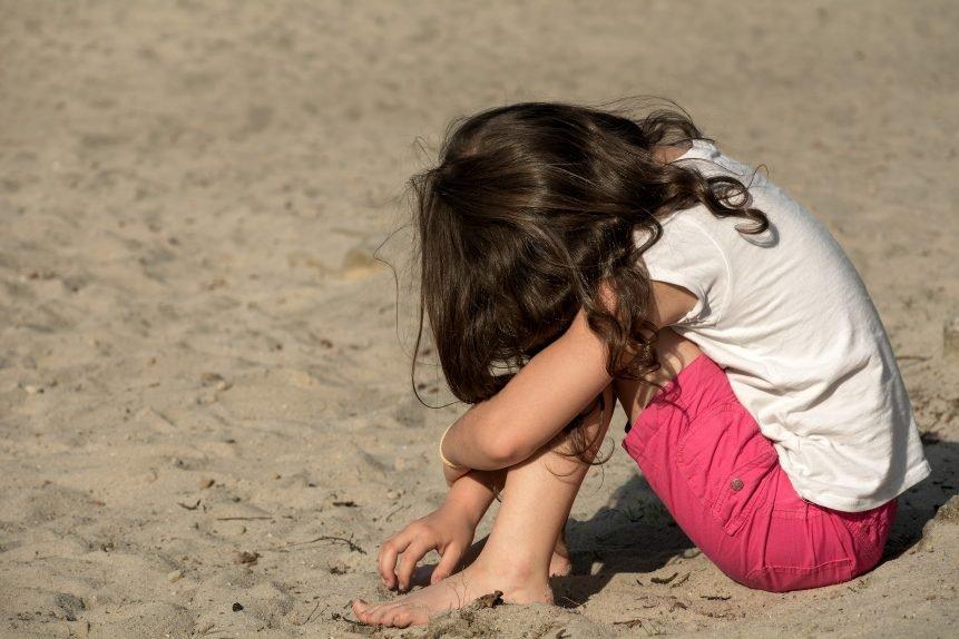 Niña sentada en el suelo con su rostro sobre las rodillas, jugando con la arena. | Imagen: Libreshot