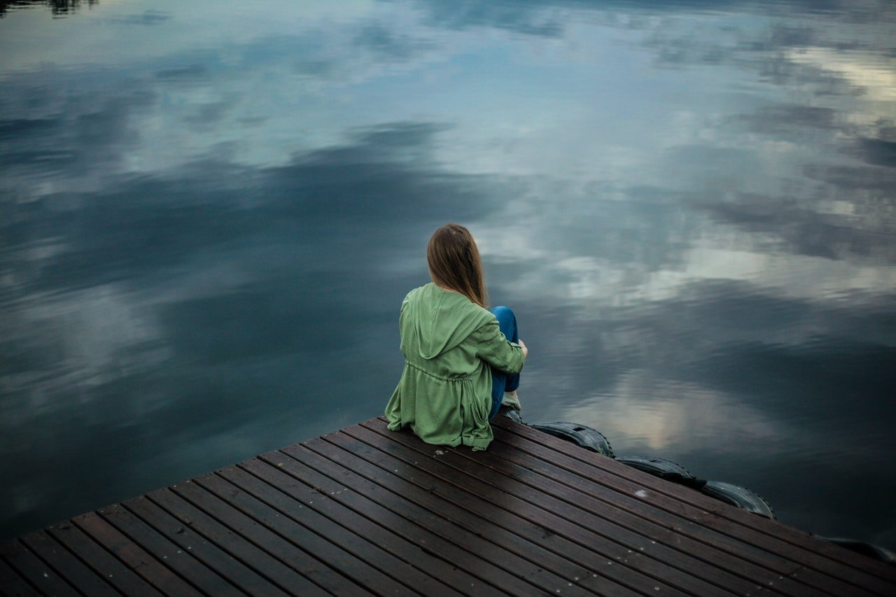 A woman thinking as she looks out over the water. | Source: Pexels.