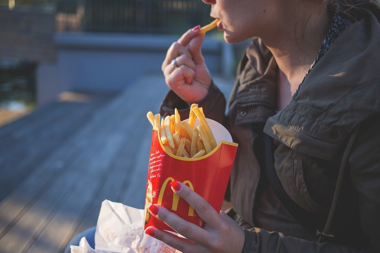 Teenager eating french fries. Image credit: Pixabay