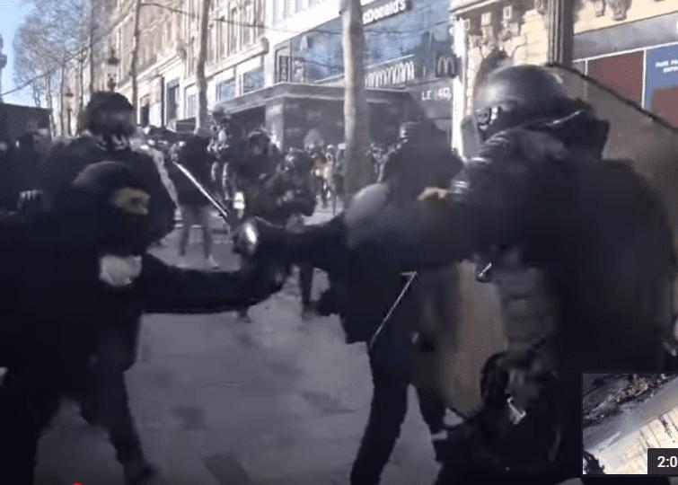 Les manifestants s'attaquent à un policier sur les Champs-Elysées, le 16 mars 2019. | Photo : Youtube/InfoCritiqueWeb