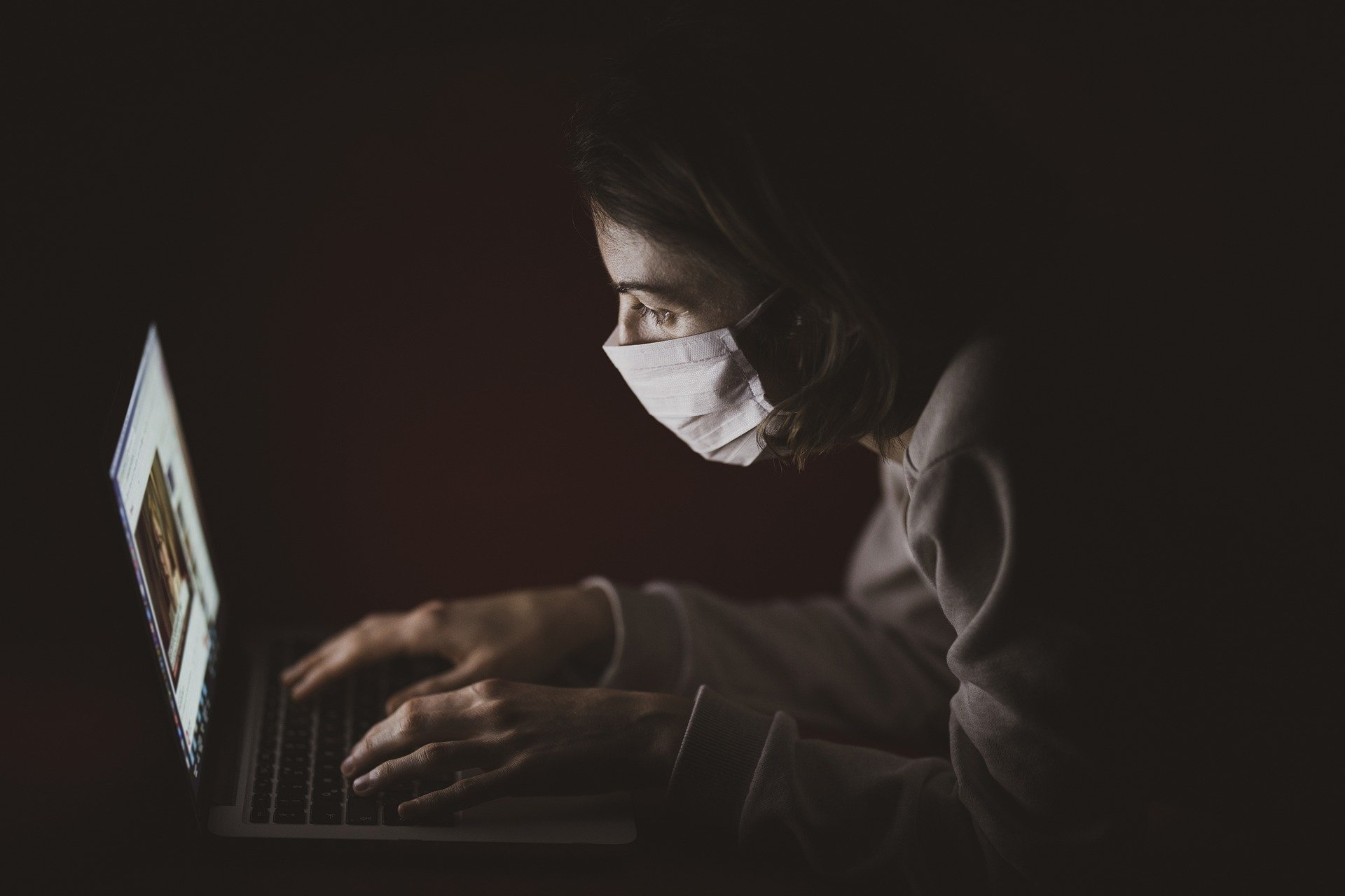 A man sitting at his laptop in the dark wearing a face mask amid the novel coronavirus pandemic. | Source: Pixabay.