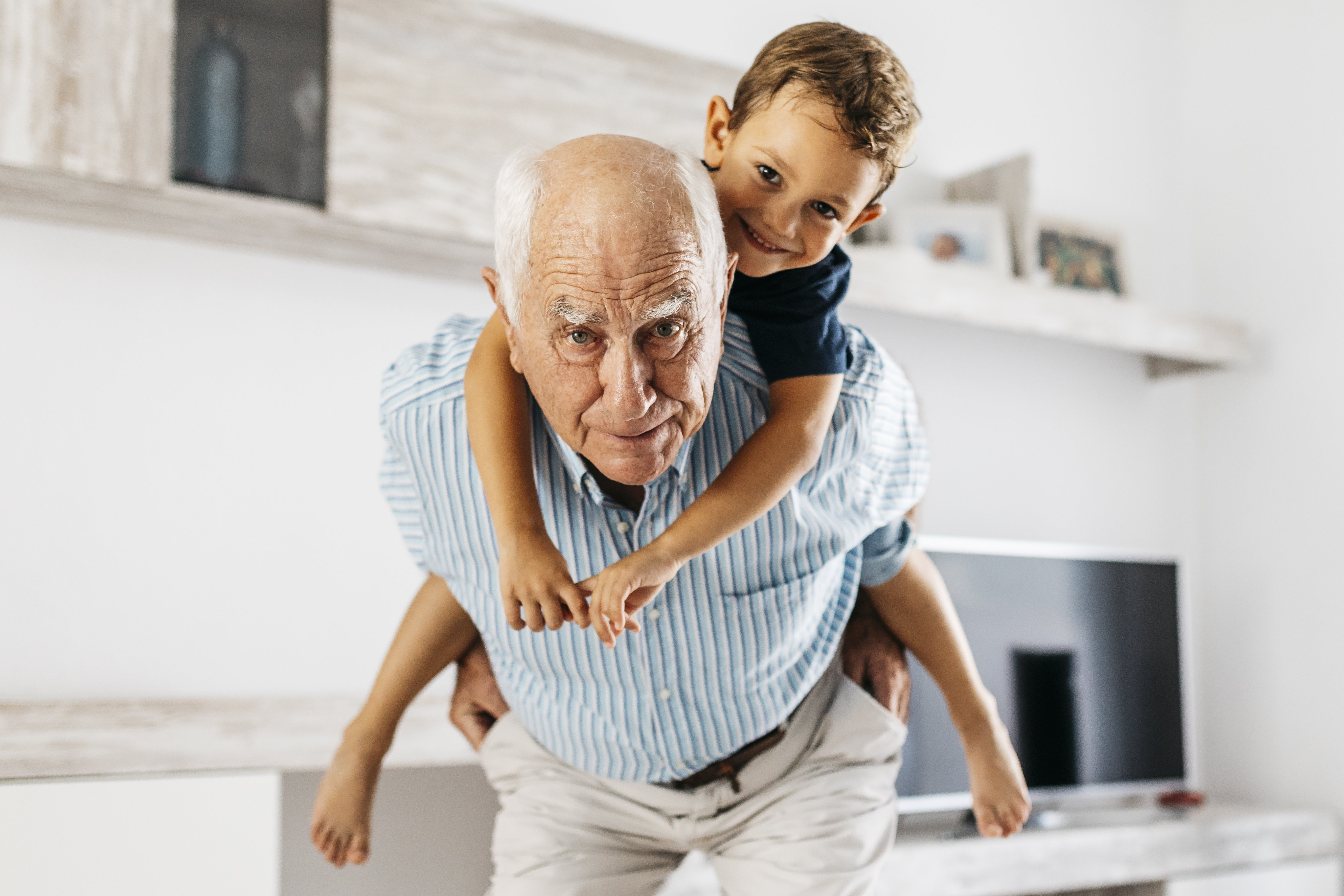 Portrait of grandfather giving his grandson a piggyback ride in the living room | Photo: Getty Images