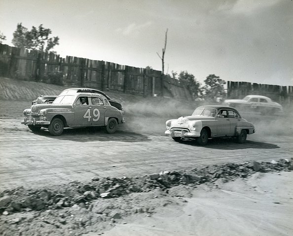 Glenn Dunaway in a 1949 Plymouth (No. 49) battles with Dick Burns during the NASCAR Cup race at Charlotte Speedway. | Photo: Getty Images
