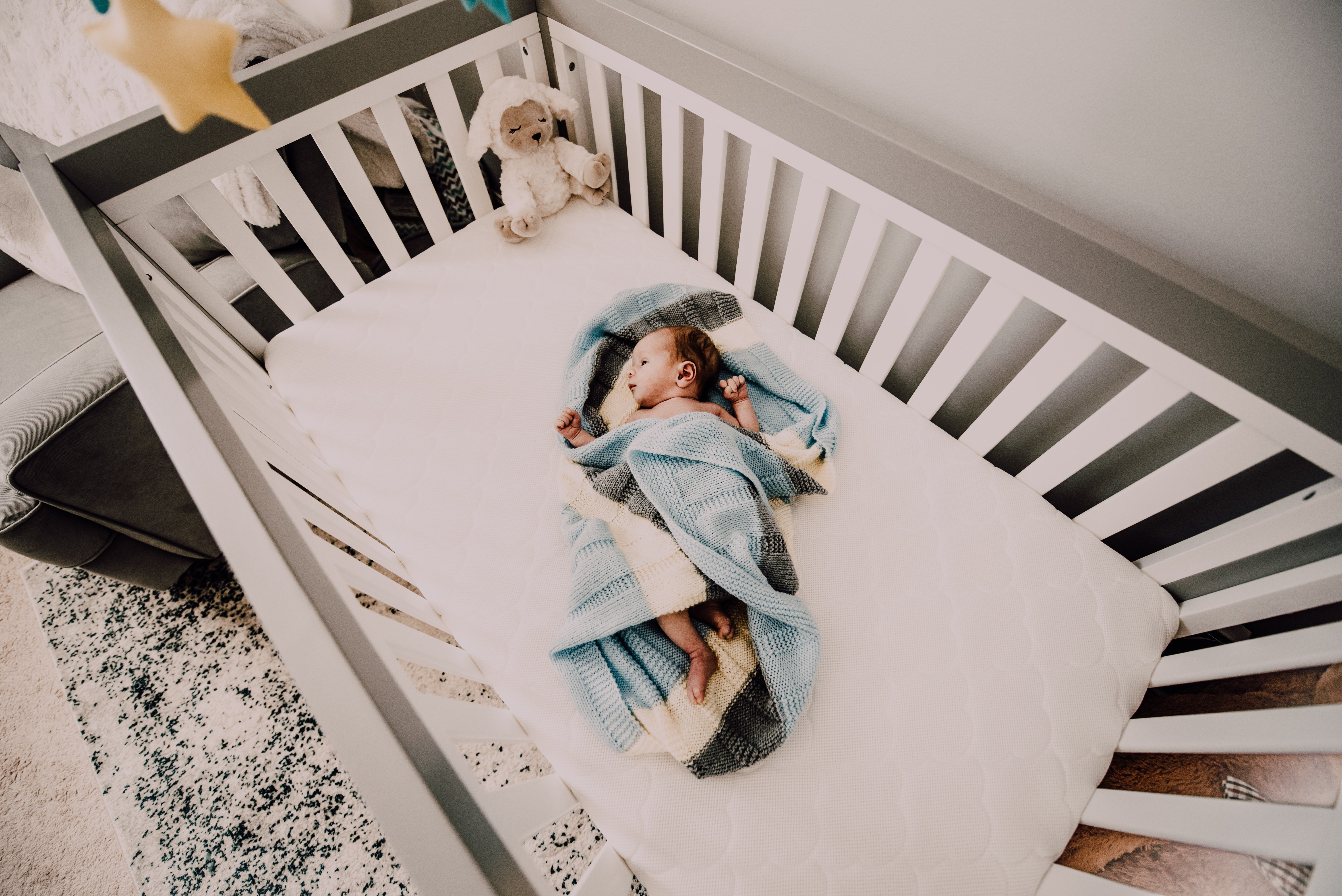 A baby wrapped in a blue blanket sleeping in a crib.   Photo: Pexels/Alicia