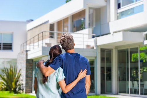 A couple embracing outside a big new house. | Source: Shutterstock.