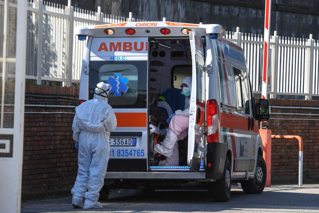 Des ambulanciers paramédicaux ouvrent une ambulance avec un patient Coronavirus COVID-19. | Photo : Getty Images