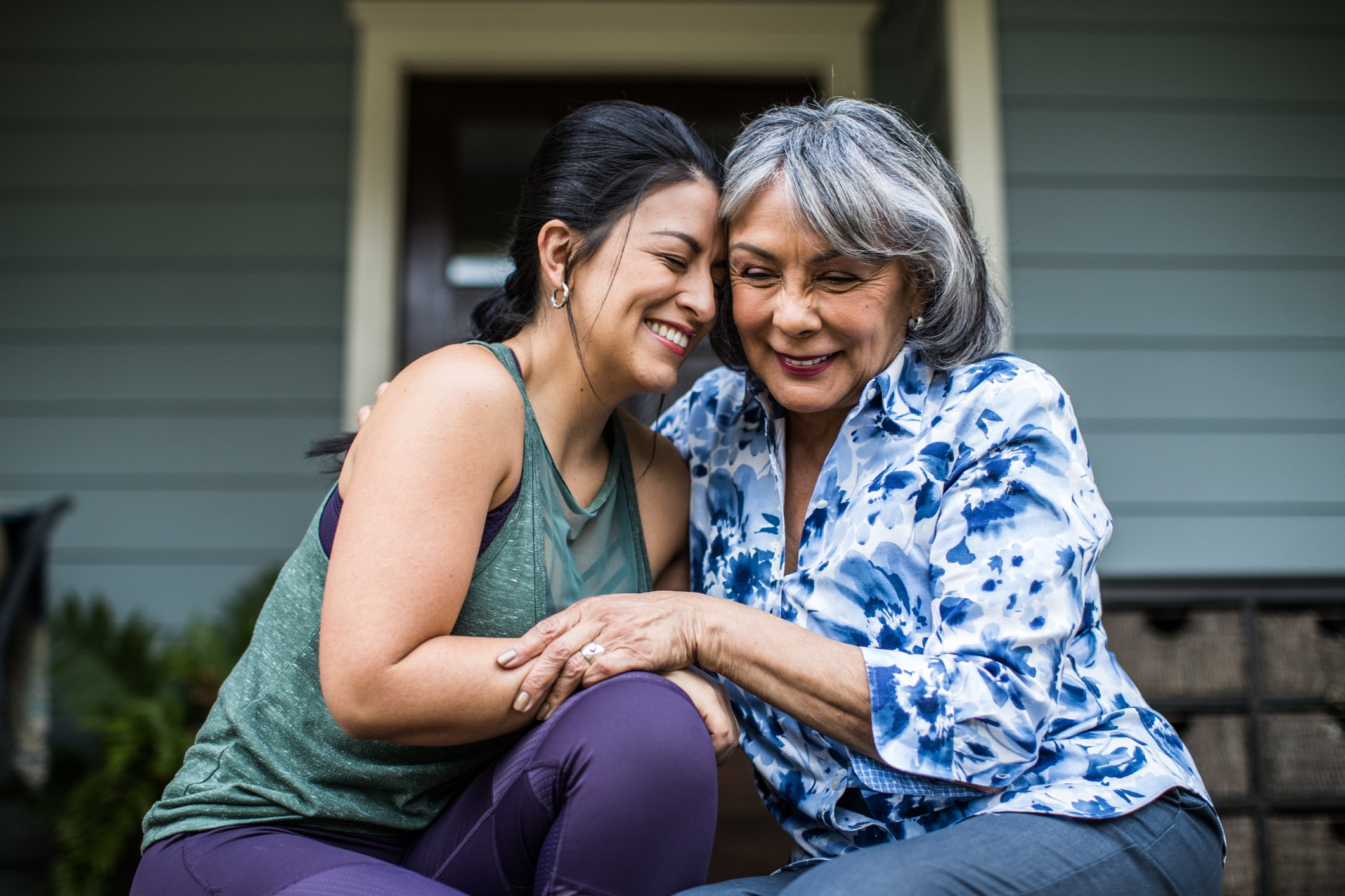 An older woman and her adult daughter laughing and hugging each other on the porch. | Source: Getty Images