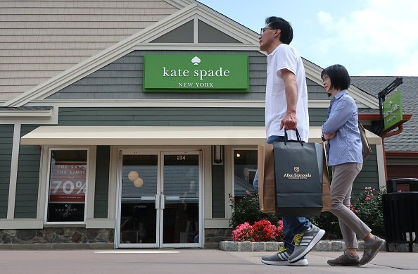A man carries a bag as he walks past the kate spade store   Photo: Getty Images
