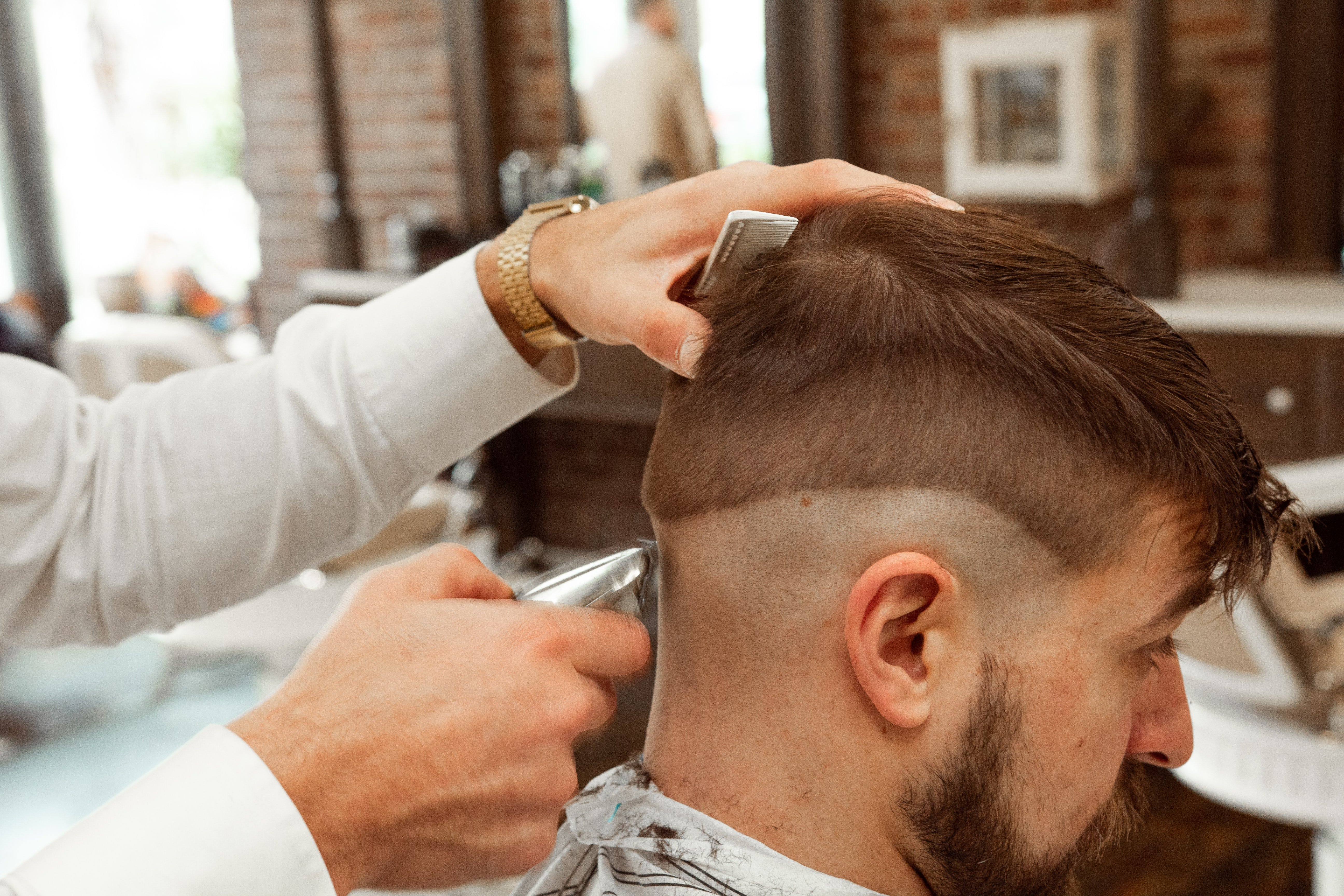 Person getting his hair shaved in a salon   Photo: Unsplash