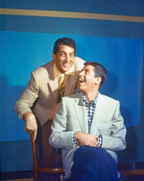 US actor and singer Dean Martin with US actor and comedian Jerry Lewis sitting on a chair in a studio portrait in 1950. | Photo: Getty Images