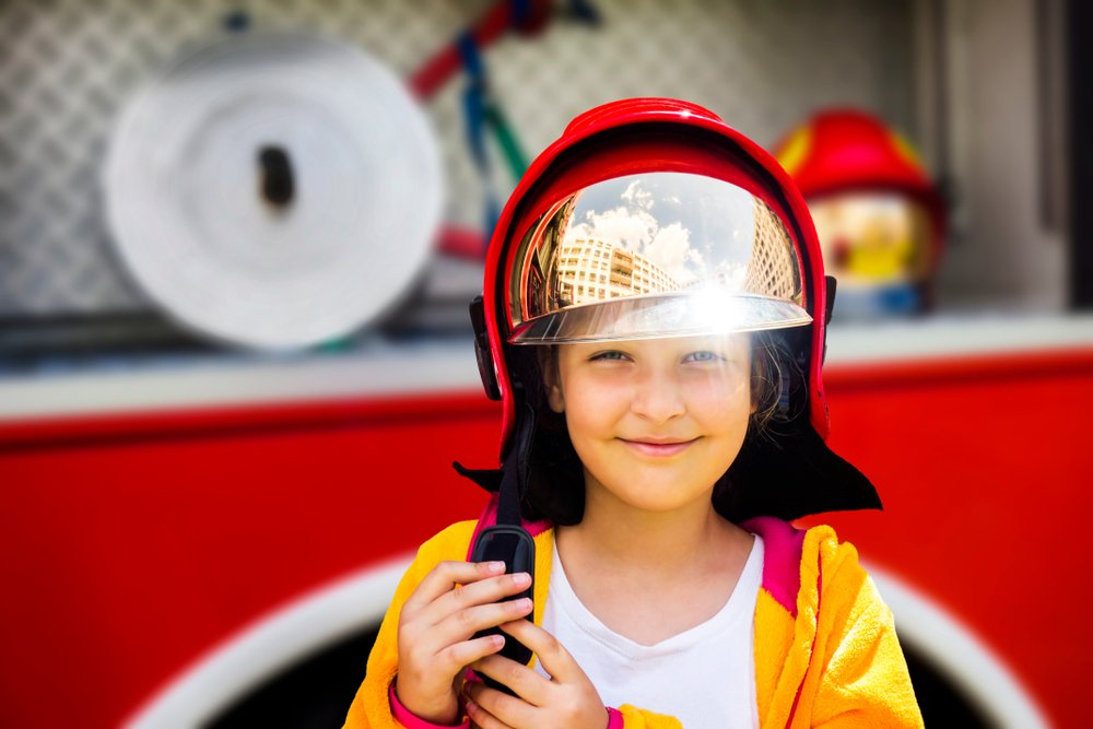 Young girl wearing a fireman's helmet and standing in front of a firetruck   Photo: Shutterstock