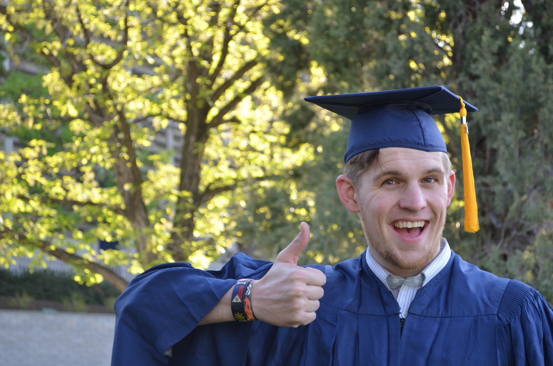 A man shows a thumbs up wearing his graduation attire and beaming with pride | Source: Pixabay