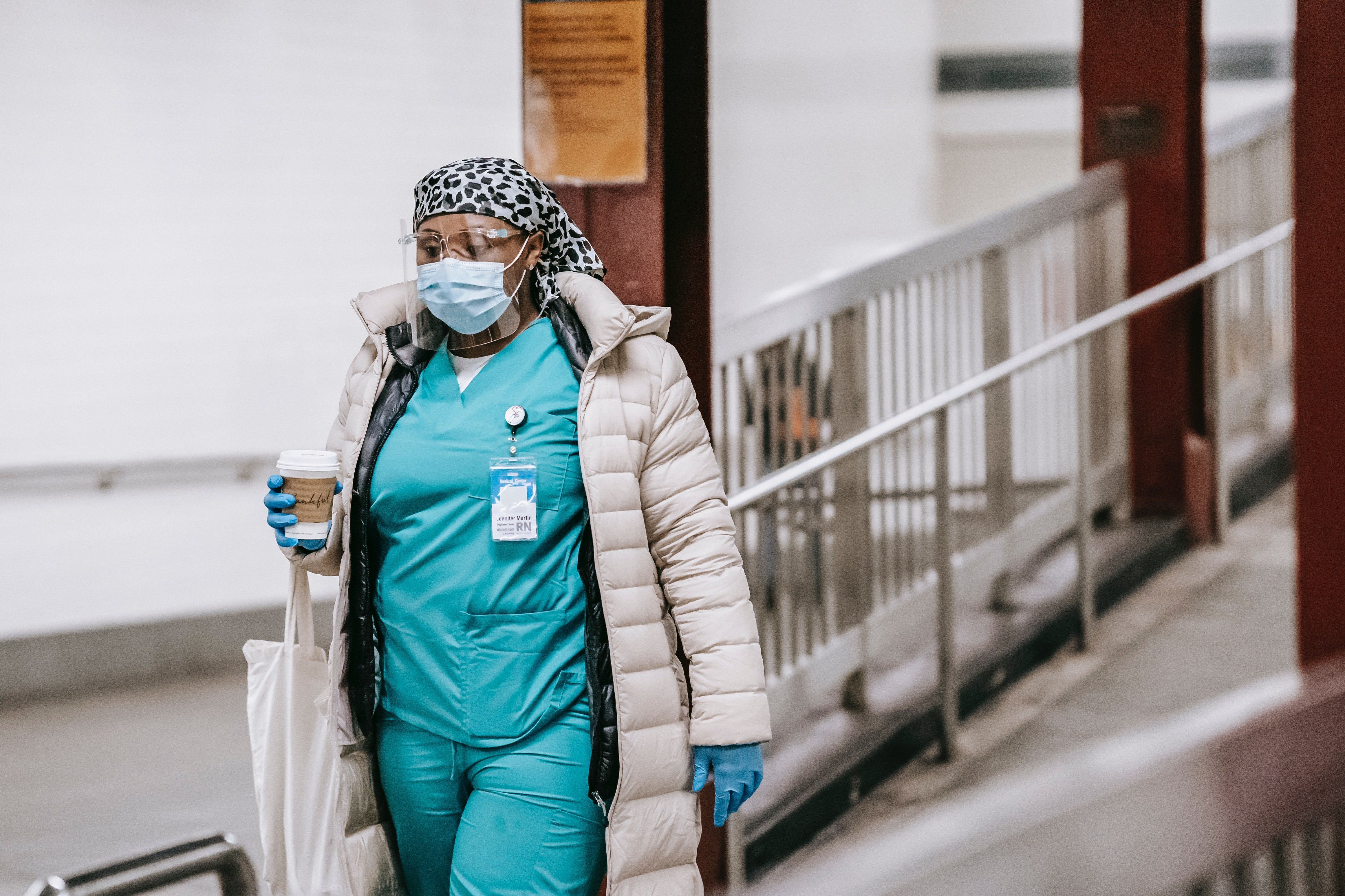 Pictured - A black female in a nurse uniform wearing protective mask and gloves | Source: Pexels