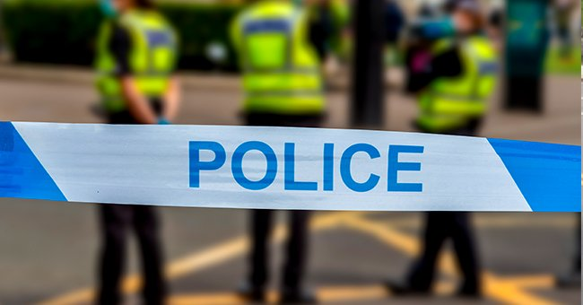 Police tape, with three police officers. | Photo: Shutterstock