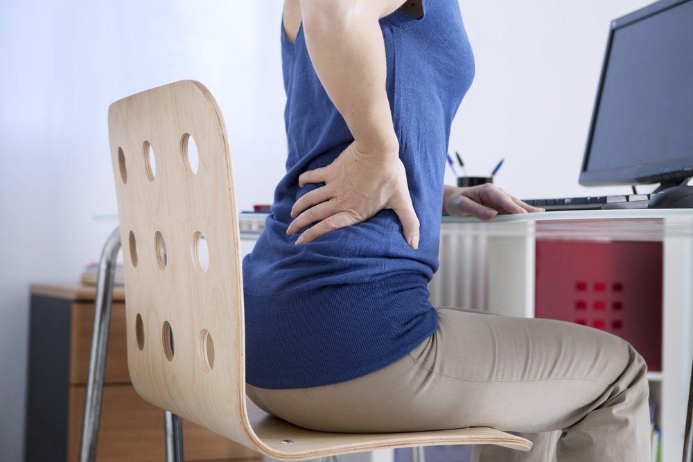 Frau am Tisch hält sich den Rücken | Quelle: Shutterstock
