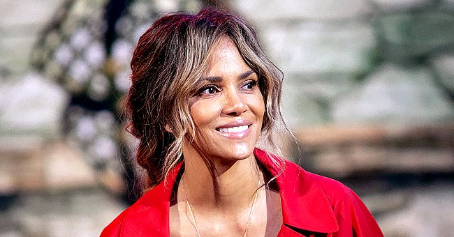Halle Berry Flaunts Her Toned Legs Posing in a Fishnet Mini Dress & Matching High-Heeled Boots