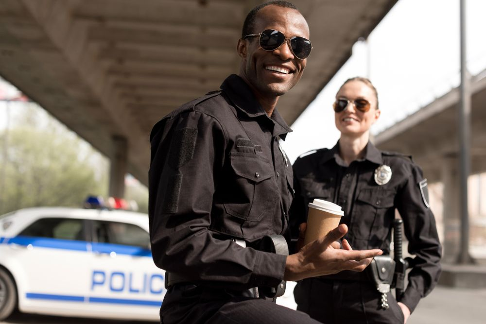 Police officers smiling during a coffee break.   Source: Shutterstock