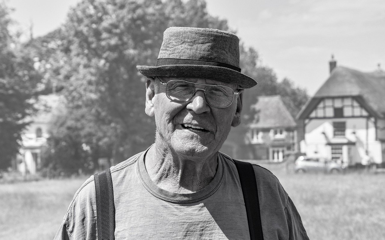 A black-and-white image of an old man wearing spectacles and a hat while standing by himself   Photo: Pixabay/shauking