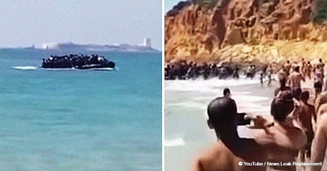 Stunned tourists watch as dozens of immigrants land on the beach before fleeing (video)