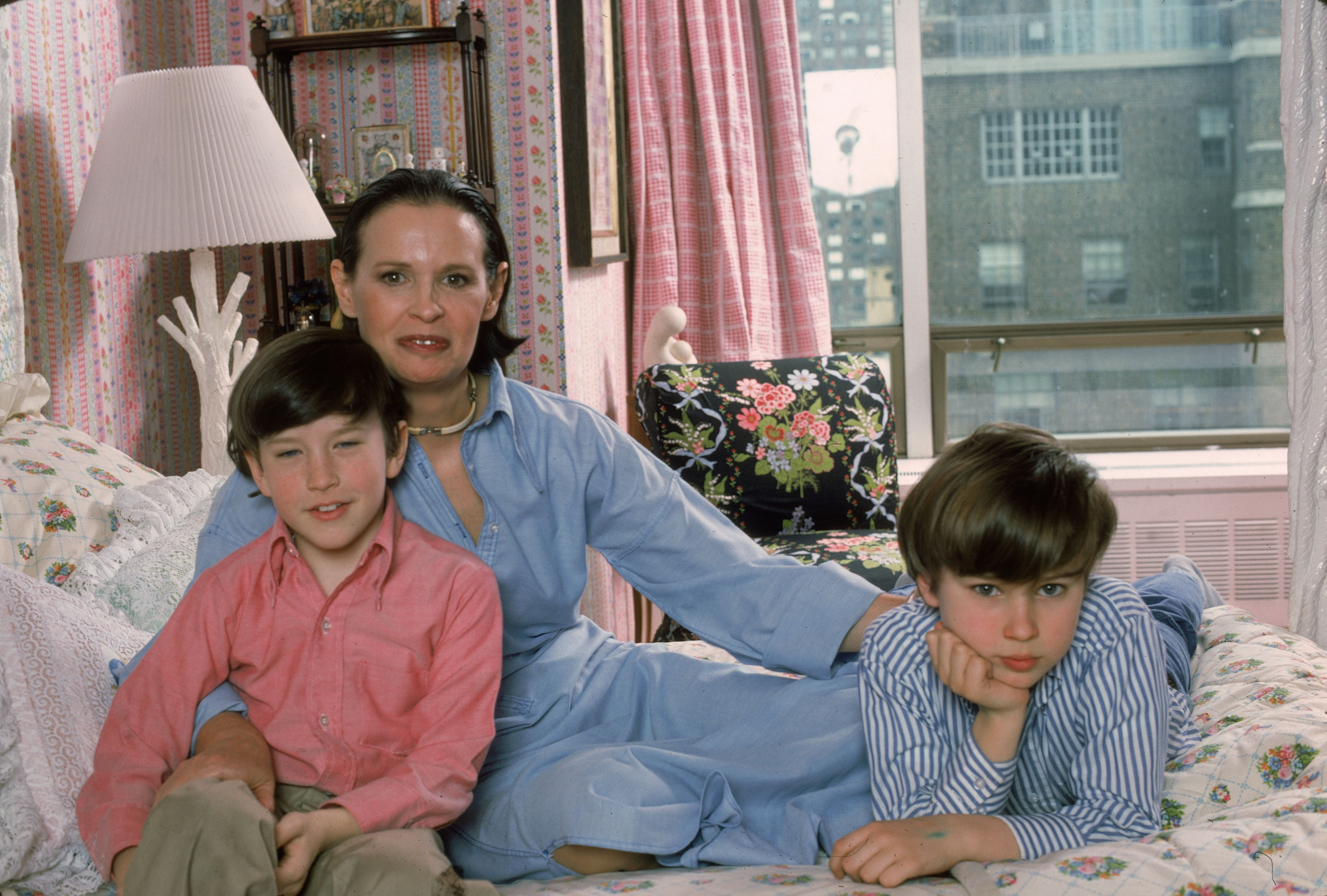 Anderson Cooper and Carter Vanderbilt Cooper with their mother Gloria Vanderbilt on Gloria's bed in their NY apartment, 1976 | Photo: Getty Images
